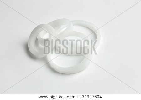 Rings of fresh onion on white background