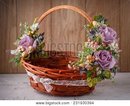 Decorative Basket Decorated With Flowers On Wooden Board