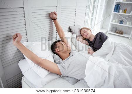 Good Morning. Appealing Glad Gay Couple Smiling While Resting In Bed And Guy Stretching