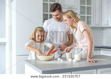 Parents Teaching Their Daughter To Cook At Kitchen