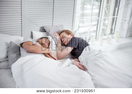 So Tired. Adorable Tranquil Gay Couple Dreaming While Resting And Lying On Pillows