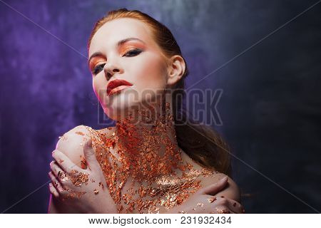 Beautiful Brunette Girl With Creative Image With Gold Foil On The Neck. Studio Portrait On Dark Back