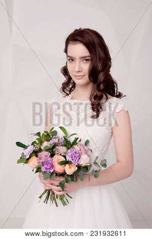 Beautiful Female Model Holding A Bouquet Of Flowers Wearing In Luxurious Long Lacy Dress Isolated On