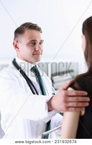 Handsome Friendly Male Doctor Talk With Thankful Female Patient At Office And Greet Her With Hand On