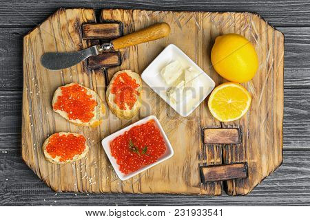 Composition with red caviar and tasty sandwiches on wooden background