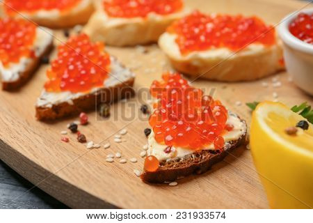 Tasty sandwiches with red caviar on wooden plate, closeup