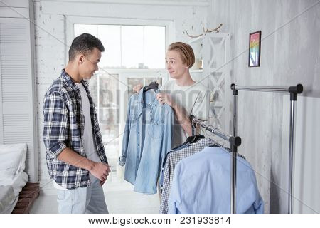 Your Style. Jovial Vigorous Gay Couple Staying In Bedroom While Selecting Clothes And Grinning