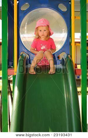 Niño mirando triste en una diapositiva del patio