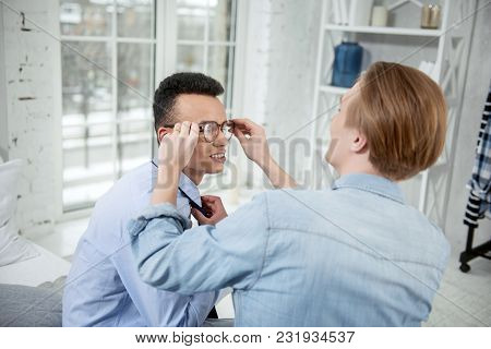 Your Glasses. Cheerful Glad Gay Couple Helping Each Other While Sitting And Posing On Blurred Backgr