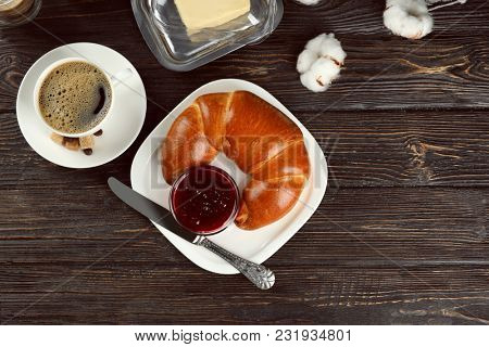 Plate with fresh tasty crescent roll, coffee and jam on wooden table