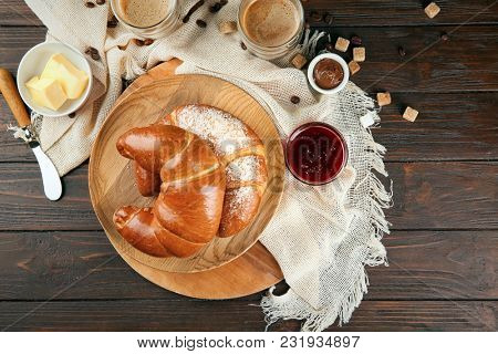 Composition with fresh tasty crescent rolls on wooden background