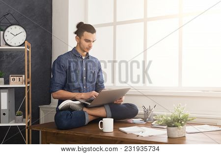 Short Break For Yoga In Office. Flexible Man Practicing Yoga At Workplace, Sitting On Desk In Lotus