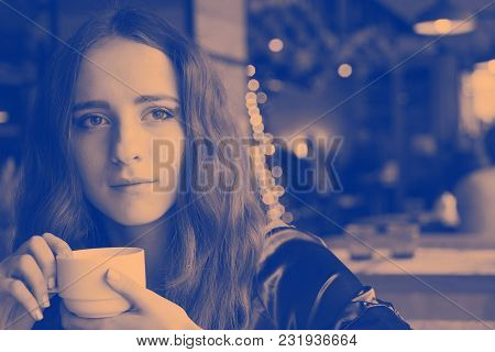 Pretty Girl Is Drinking Coffee In A Cafe. She Is Sitting At A Table And Looking Through The Window.