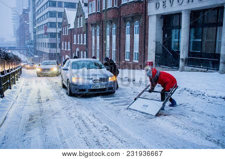 Birmingham, United Kingdom - March 02 2018 : Unidentified Woman Removing Snow From Road To Help A Ca