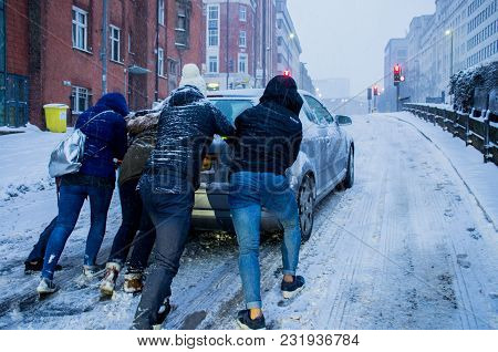 Birmingham, United Kingdom - March 02 2018 : Unidentified People Pushing A Car Which Is Slipping Dur