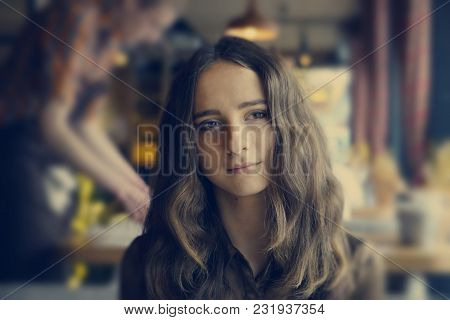 Thoughtful Beautiful Girl Sitting In A Cafe. She Has Big Brown Romantic Eyes. With Nice Brown Long H