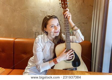 Young Smiling Hipster Woman Sitting Playing Guitar At Cafe. Girl Learning To Play Song