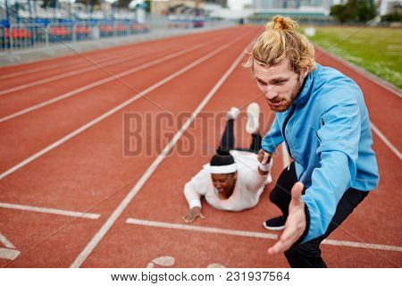 Young man pulling oversized female down racetrack towards finish line