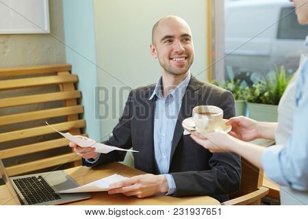 Young businessman with papers smiling to waitress giving him cup of aromatic herbal tea