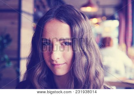 Romantic Looking Girl In A Cafe. With Big Brown Beautiful Eyes. With Nice Brown Long Hair. Wearing A