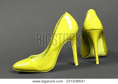 Lacquered Yellow High Heels Shoes On Gray Background.