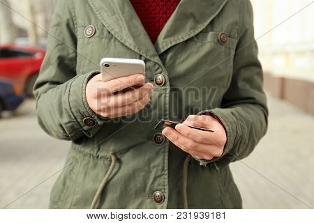 Woman with credit card using smartphone outdoors