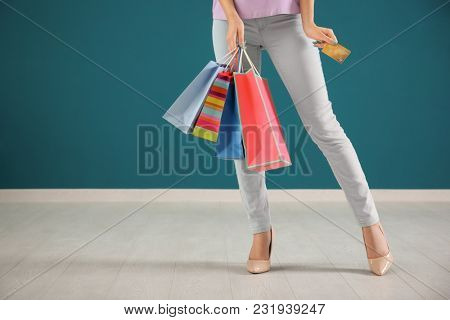 Young woman with credit card and shopping bags against color wall