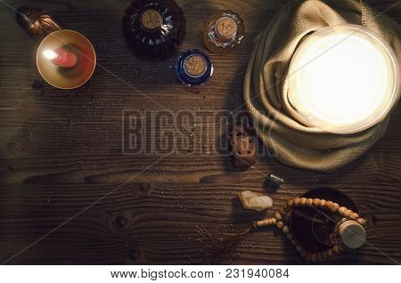 Crystal Ball And Magic Potions On Fortune Teller Magic Desk Table Background With Copy Space. Seance