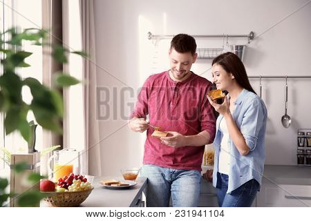 Young couple having breakfast with toasts in kitchen