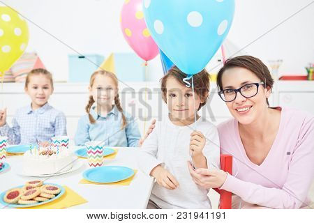 Happy teacher and little boy with blue balloon looking at camer aby festive table at birthday party