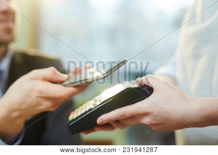 Businessman with smartphone paying through mobile transfer system or app