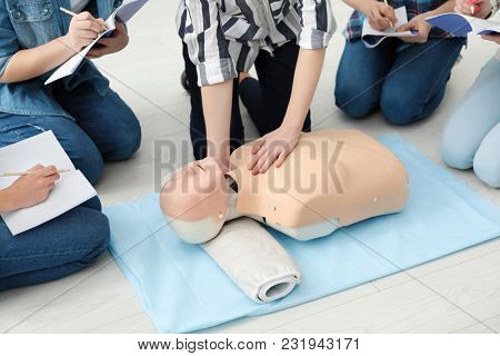 Group of people practicing CPR on mannequin at first aid class