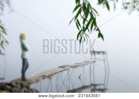 Beautiful Young Woman On A Wooden Bridge On The River Admiring The Sunrise And Fog. Beautiful Blur B