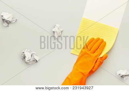 Hand In Protective Rubber Glove With Yellow Rag And Crumpled Papers. Woman Washing White Surface Wit