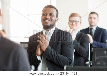 Row of businessmen clapping hands while congratulating speaker on success after presentation