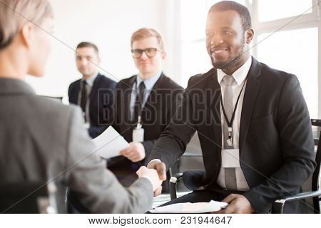 African-american broker in formalwear congratulating one of speakers on successful report at conference