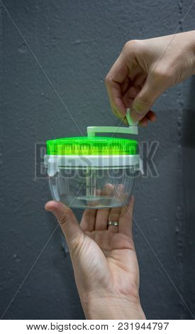 Hand Holding Empty Plastic Container Of Mini Kitchen Tools For Manual Food Chopper With Green Lid Ag