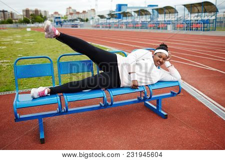 Young active woman in white sweatshirt, leggins and cross-shoes lying on bench and raising leg