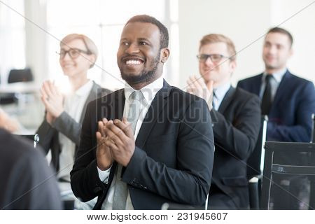 Happy businessman and his colleagues clapping hands at conference after report of speaker