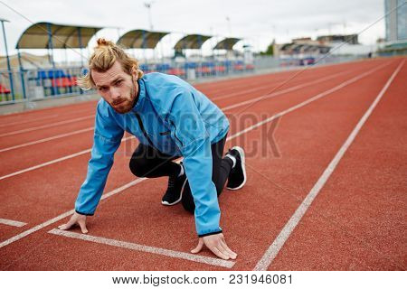 Young sportsman looking at camera while standing by start line and getting ready to run