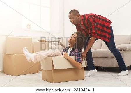 Happy African-american Couple Unpacking Moving Boxes And Having Fun In New Apartment. Man Riding Wom