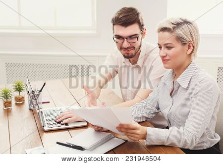 Smiling Couple Of Young Colleagues Working In Modern Office. Two Coworkers Discussing Their Work, Wo