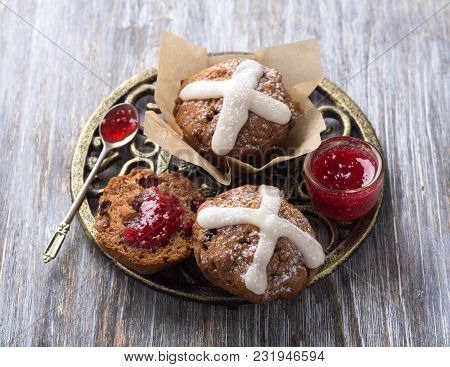 Easter Cross Muffins With Raisins, Cranberries And Raspberry Jam On A Wooden Table