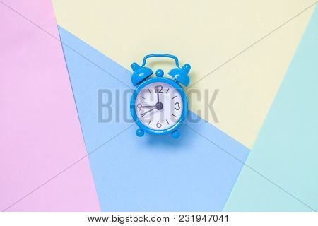 Small Blue Alarm Clock On Colorful Pastel Background Flat Lay Creative Minimal Concept.