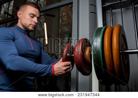 Young athlete putting heavy disks on weightlifting bar before training
