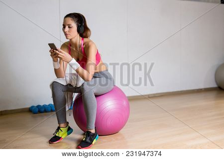 Young restful female in sportswear sitting on fitball at break and listening to tracks from playlist in smartphone