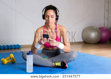 Relaxed young sportswoman with headphones and smartphone listening to music from playlist between workouts
