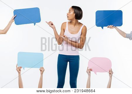 My Opinion. Nice Pleasant Young Woman Standing Against The White Background And Pointing At The Sign
