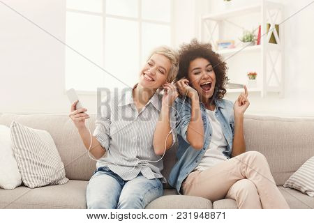 Two Women Listening Music Online On Smartphone And Sharing Earphones Sitting On Couch At Home, Copy