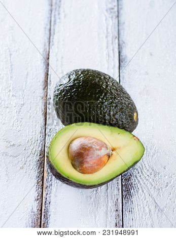 Organic Avocados On A White Wooden Background. Healthy Vegan Food